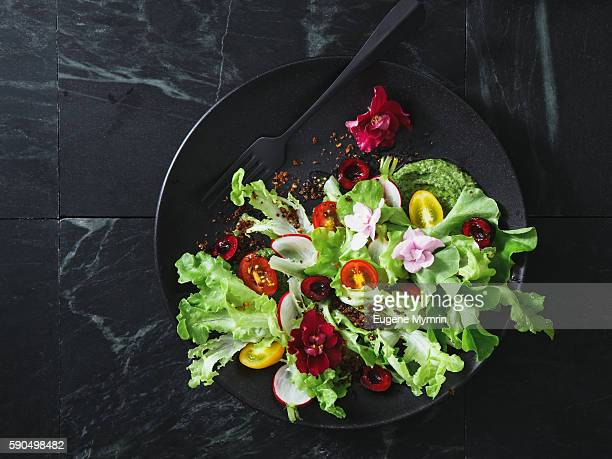 Salad with lettuce, cherry tomatoes, granola, violets and arugula sauce