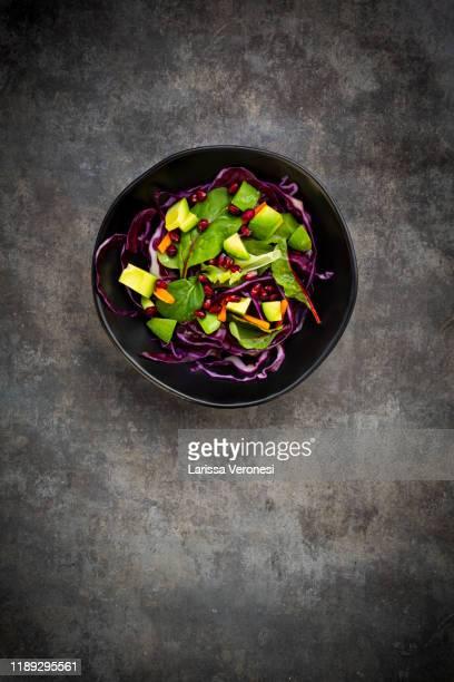 salad with red cabbage, avocado and pomegranate seeds - larissa veronesi stock-fotos und bilder
