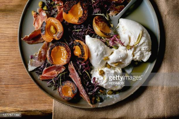 Salad with traditional italian burrata cheese. Black arugula. Grilled apricot. Prosciutto. Pistachio nuts and olive oil in plate on textile napkin...