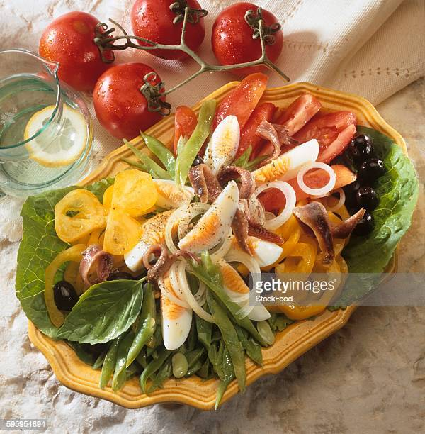 salade ni??oise with anchovies - oise stock photos and pictures
