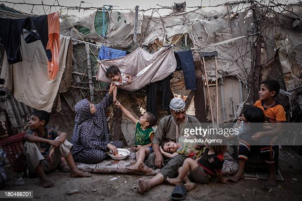 Salah el-Vaddiye, one of his wifes and 7 of his children sitting out front of their two-roomed slum on September 4, 2013 in Ein al-Zeitun village,...