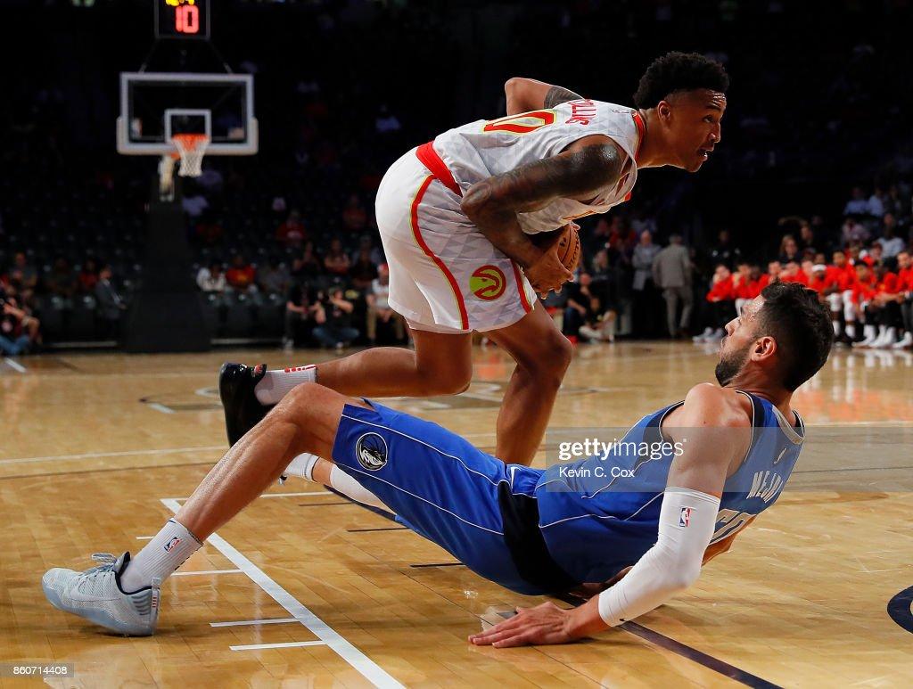Salah Mejri #50 of the Dallas Mavericks falls as John Collins #20 of the Atlanta Hawks drives the basket at McCamish Pavilion on October 12, 2017 in Atlanta, Georgia.