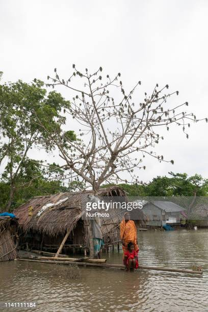 Salam Sheikh with his family menbers stands on a log in front of their home surrounded by high waters in Khulna on May 4 as Cyclone Fani reached...