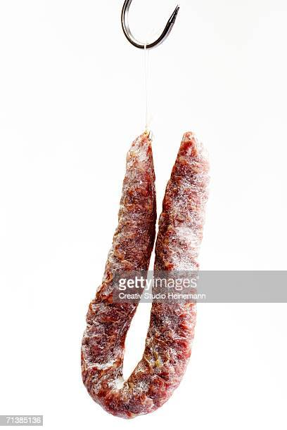 salami hanging on butcher hook, close-up - pepperoni stock photos and pictures
