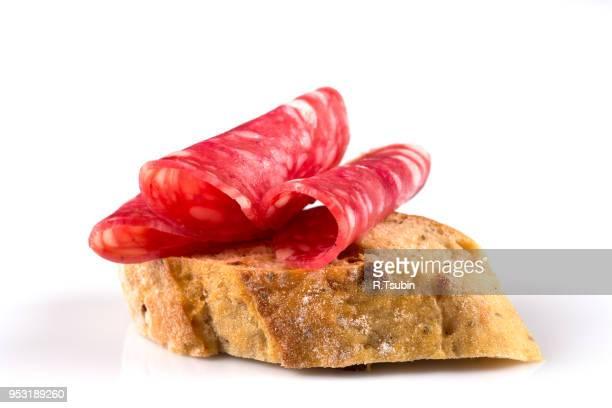 salami on ciabatta. sandwich of salami slices on whole grain bread. - crosta di formaggio foto e immagini stock
