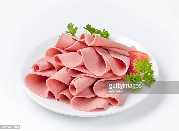 salami slices on white plate - baloney stock photos and pictures