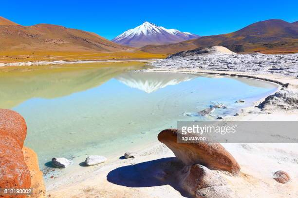 salar de talar and miniques snowcapped volcano - turquoise lake mirrored reflection and piedras rojas (red stones) rock formation at sunrise, idyllic atacama desert, volcanic landscape panorama – san pedro de atacama, chile, bolívia and argentina border - chile stock pictures, royalty-free photos & images