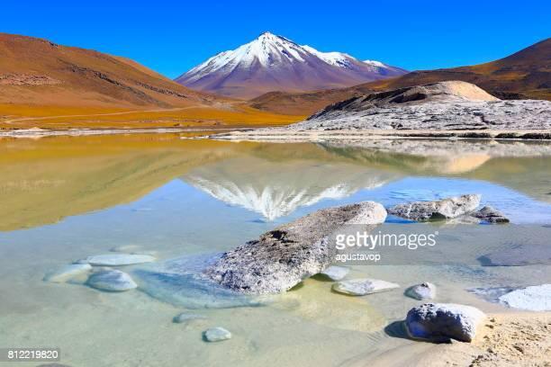Salar de Talar und Miniques schneebedeckten Vulkan - gespiegelt türkisblauen See, Reflexion und Piedras Rojas (roten Steinen) Felsformation bei Sonnenaufgang, idyllische Atacama-Wüste, vulkanische Landschaft Panorama – San Pedro de Atacama, Chile, Bolivien und Argentinien Grenze