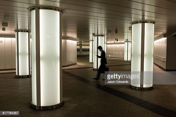 A salaryman checking his cell phone walking past light pillars in a subway.
