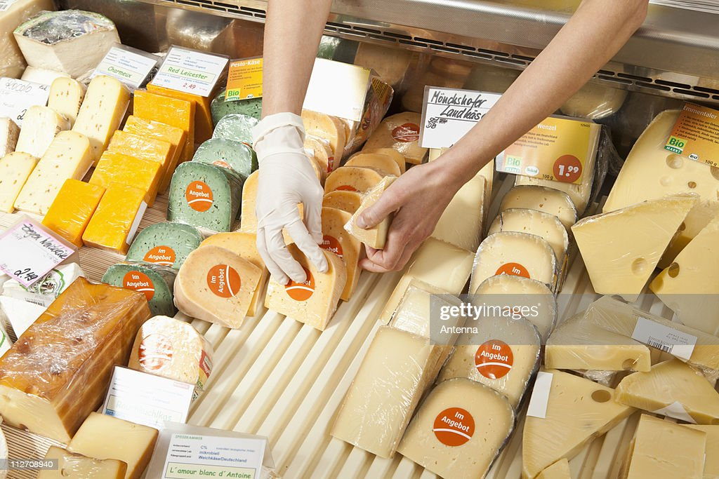 A sale clerk in a cheese shop, focus on hands : Stock Photo