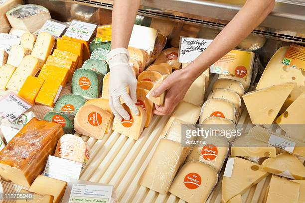 a sale clerk in a cheese shop, focus on hands - delicatessen stock pictures, royalty-free photos & images