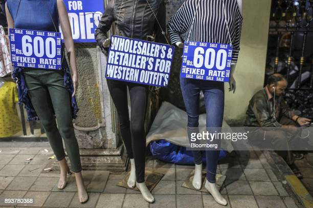 Sale signs are displayed on mannequin outside a clothing store in Mumbai India on Friday Dec 15 2017 India's inflation surged past the central bank's...