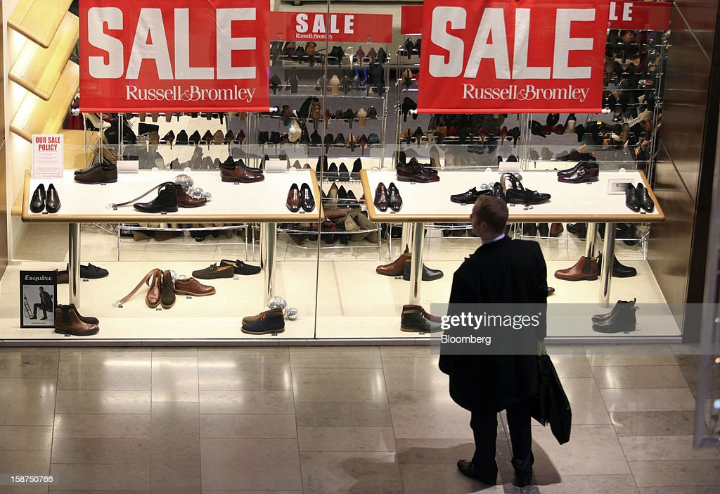 Sale signs sit above a display of footwear displayed in the window of a Russell & Bromley shoe store at the Westfield Stratford City shopping mall in London, U.K., on Thursday, Dec. 27, 2012. Overall Christmas shopping in the U.K. was similar to last year, according to the British Retail Consortium. Photographer: Chris Ratcliffe/Bloomberg via Getty Images