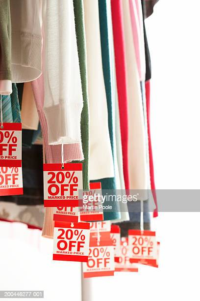 Sale tags attached to hanging clothes, close-up