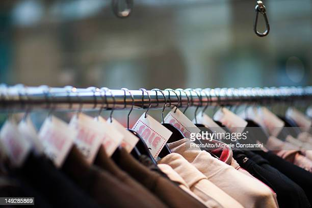 Sale tags on clothing in store, cropped
