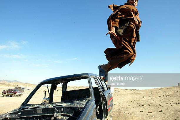 Saleh Mohammad Khan jumps off the wreckage of a truck that had been used by United States special force troops on December 5th before being blown...