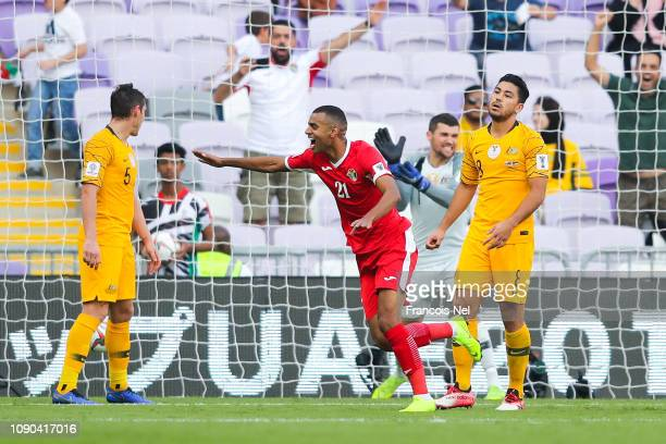 Salem AlAjalin of Jordan celebrates past dejected Massimo Luongo and Mark Milligan of Australia after Anas Bani Yaseen of Jordan scored his team's...
