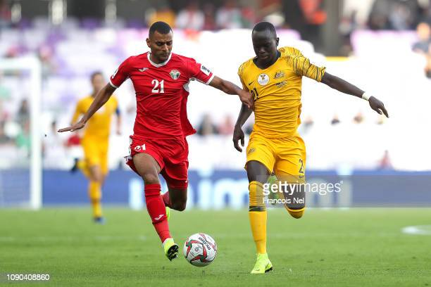 Salem AlAjalin of Jordan competes for the ball with Awer Mabil of Australia during the AFC Asian Cup Group B match between Australia and Jordan at...