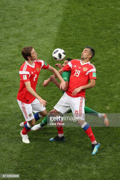 Salem Aldawsari of Saudi Arabia is challenged by Mario Fernandes and Alexandr Samedov of Russia during the 2018 FIFA World Cup Russia Group A match...
