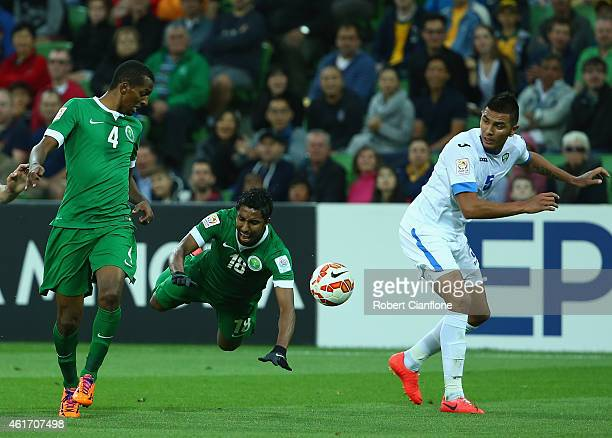 Salem Aldawsari of Saudi Arabia is fouled by Anzur Ismailov of Uzbekistan during the 2015 Asian Cup match between Uzbekistan and Saudi Arabia at AAMI...
