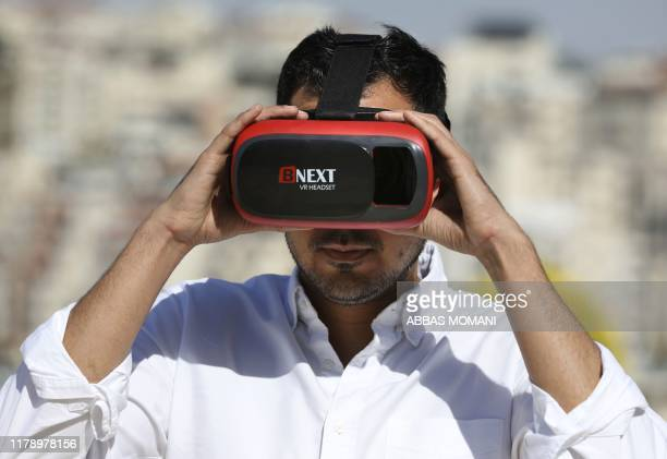 "Salem Barameh, executive director of the Palestine Institute for Public Diplomacy, uses a headset for the ""Palestine VR"", a new application allowing..."
