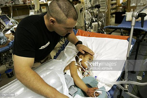 Task force med Lieutnant Anthony Sibilia checks the condition of 3years old Afghan boy Azada Khan who was seriously injured after a Taleban mortar...