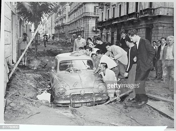 Salerno residents are trying to extricate an auto from the mud that engulfed it during this week's disaster in Salerno Torrential rains were followed...