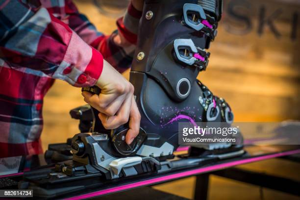 Sales Assistant adjusting ski boots and binding on skis.