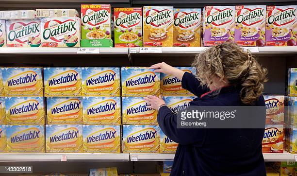 A sales assistant adjusts packets of Weetabix breakfast cereal produced by Weetabix Ltd in this arranged photograph inside a supermarket in Slough UK...