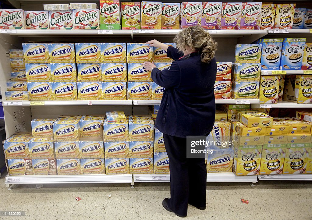 A sales assistant adjusts packets of Weetabix breakfast cereal, produced by Weetabix Ltd., in this arranged photograph inside a supermarket in Slough, U.K., on Monday, April 23, 2012. Bright Food Group Co., China's second-largest food company, denied media reports that it is in talks to buy British cereals maker Weetabix Ltd. from private equity firm Lion Capital. Photographer: Jason Alden/Bloomberg via Getty Images