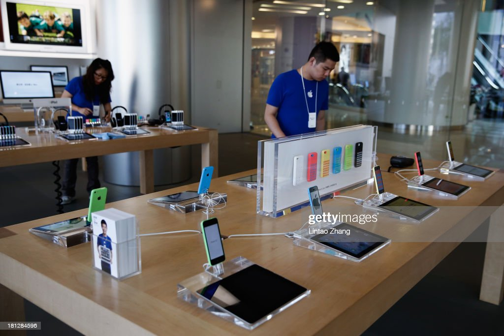 Sales assistant arranges new Apple iPhone 5c smartphones at the Wangfujing flagship store on September 20, 2013 in Beijing, China. Apple launched the new iPhone 5C model that will run iOS 7 is made from hard-coated polycarbonate and comes in various colors and the iPhone 5S that features fingerprint recognition security.