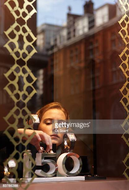 A sales assistant arranges the jewellery on display in the window of jewellers 'Boucheron' on Old Bond Street on November 22 2008 in London England...