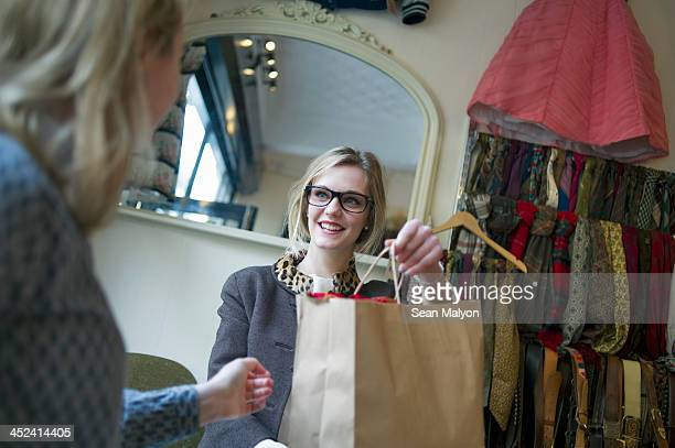 sales assistant handing shopping bag to lady - sean malyon stock pictures, royalty-free photos & images