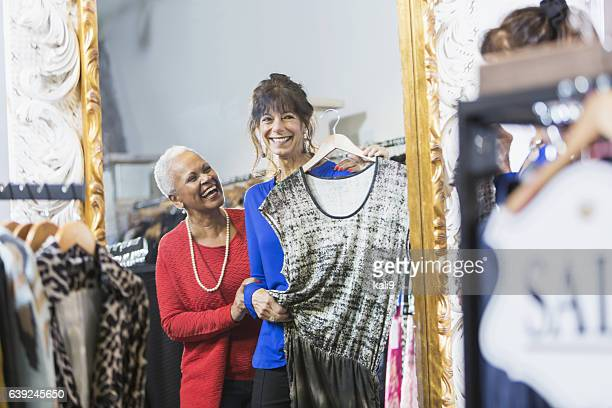 Sales assistant helping customer in clothing store