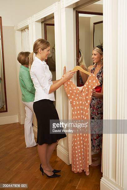 Sales assistant holding dress for woman in changing room