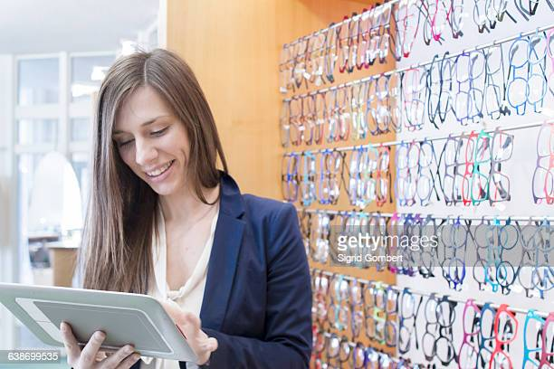 sales assistant in opticians using digital tablet smiling - sigrid gombert stock pictures, royalty-free photos & images