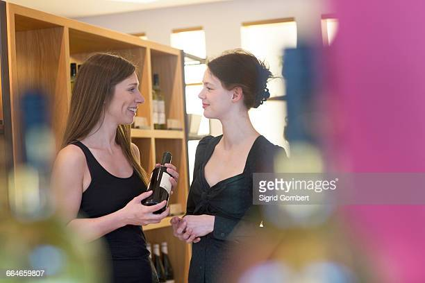 sales assistant in wine shop recommending bottle of wine to customer - sigrid gombert stock pictures, royalty-free photos & images