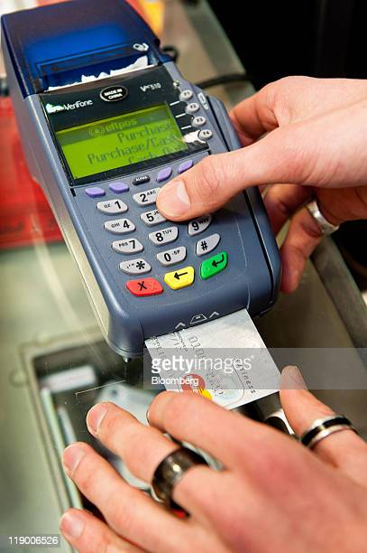 A sales assistant processes a credit card payment using an Eftpos machine in Wellington New Zealand on Wednesday July 13 2011 New Zealand's first...