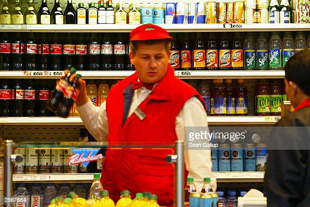 A sales assistant pulls down two bottles of CocaCola from a shelf stacked mostly with returnable bottles and cans at a fast food sales kiosk October...