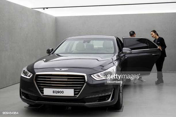 A sales assistant right assists a customer as he inspects a Hyundai Motor Co Genesis EQ900 sedan at the newly opened Genesis showroom in the Gangnam...