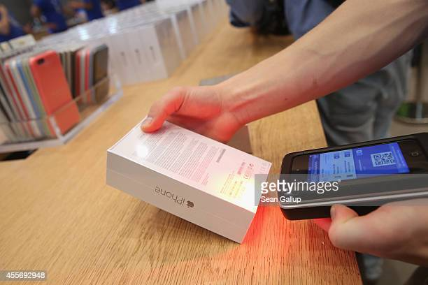 A sales assistant scans new Apple iPhone 6 phones at the Apple Store on the first day of sales of the new phone in Germany on September 19 2014 in...
