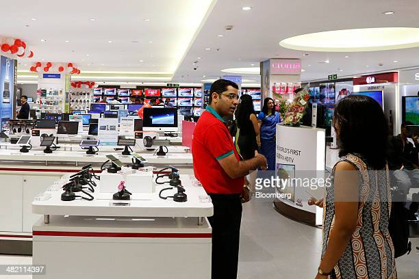 A sales assistant speaks to a customer at a Croma electronics megastore operated by Tata Group's Infiniti Retail unit during its official opening in...