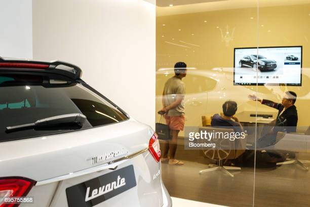 A sales assistant speaks to customers near a Maserati Levante vehicle at a Maserati SpA showroom in Singapore on Sunday June 4 2017 Singapores...