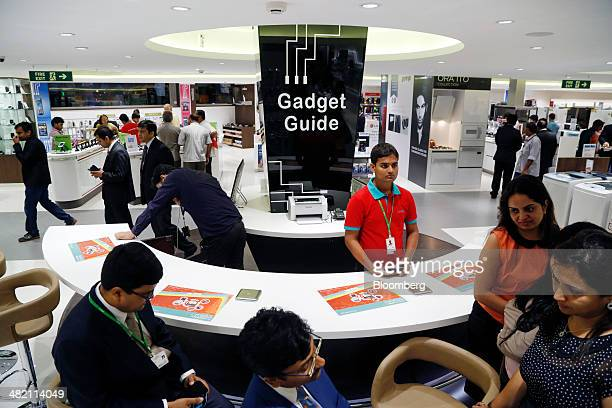 A sales assistant stands at the 'Gadget Guide' customer information counter while customers browse merchandise at a Croma electronics megastore...