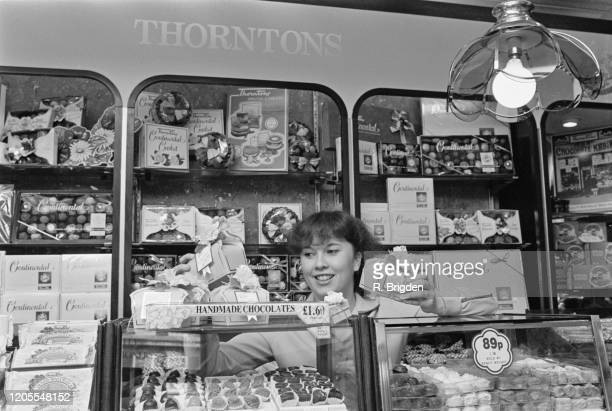 A sales assistant stands behind a display of handmade chocolates with boxes of chocolates on shelves behind in a branch of Thorntons confectioners...