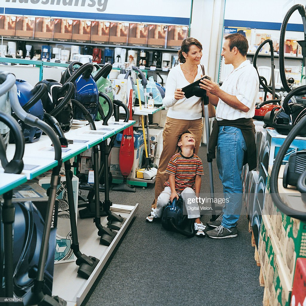 Sales Assistant Talking to a Woman and Her Son About a Vacuum Cleaner in a Department Store : Stock Photo