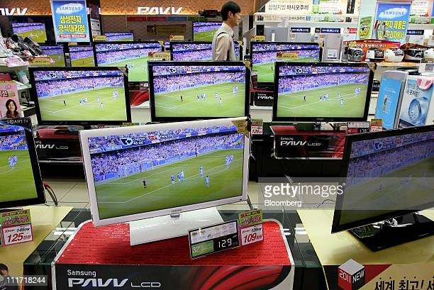 A sales assistant walks past Samsung Electronics Co lightemitting diode televisions and liquidcrystal display televisions at an electronic store in...