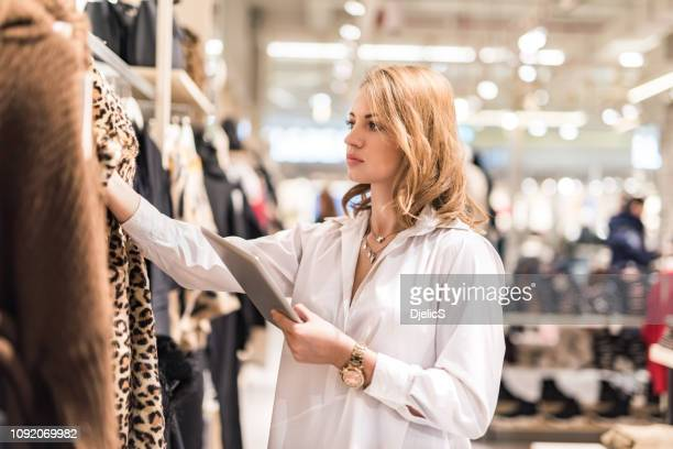 sales assistant with a digital tablet examining products in a clothing store. - fashion industry stock pictures, royalty-free photos & images