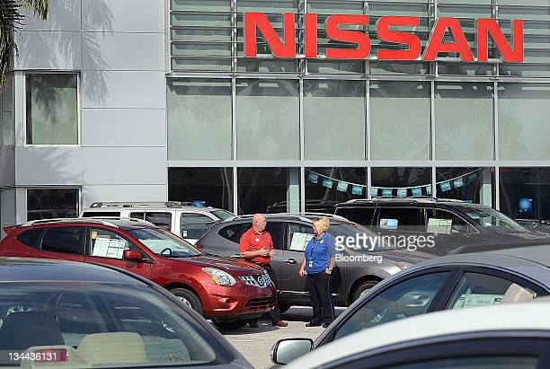 Sales associate Bob Stevens left helps customer Christie LaVoie shop for a 2012 Nissan Motor Co Rogue vehicle at Royal Palm Nissan car dealership in...