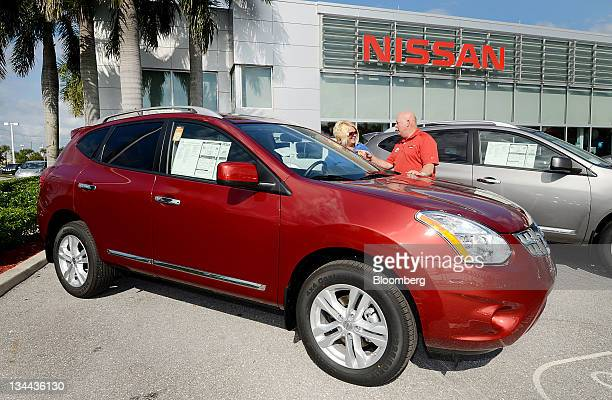 Sales associate Bob Stevens right helps customer Christie LaVoie shop for a 2012 Nissan Motor Co Rogue vehicle at Royal Palm Nissan car dealership in...